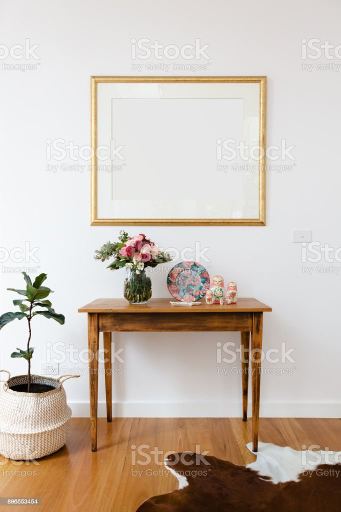 Blank picture frame above a side table with flowers and pot plant stock photo