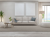 istock Blank picture frame near beige sofa on brown carpet of large living room in modern house or luxury pool villa. 1271347141