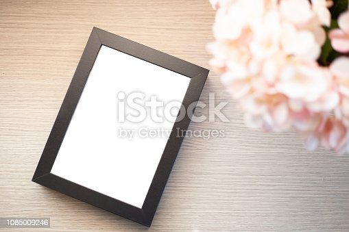 istock Blank picture frame on table 1085009246