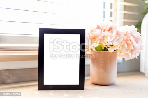 istock Blank picture frame on table 1085009254