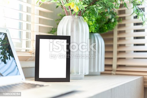 istock Blank picture frame on table 1085009284