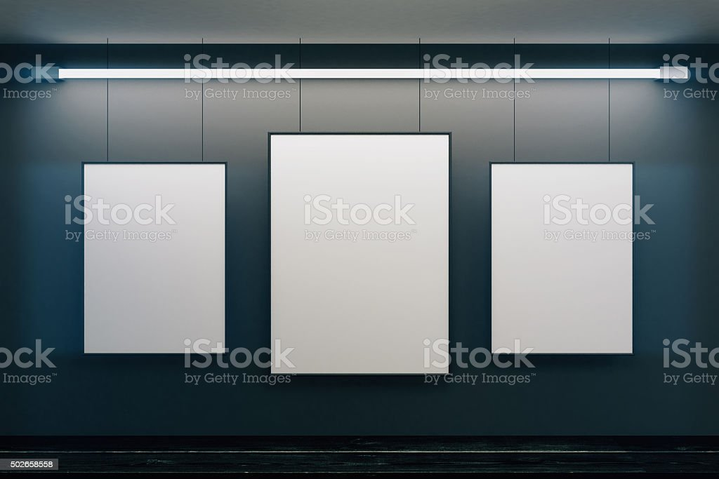 Blank picture frames on black walls with black wooden floor stock photo