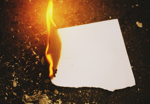 A blank piece of paper is burning to ashes.