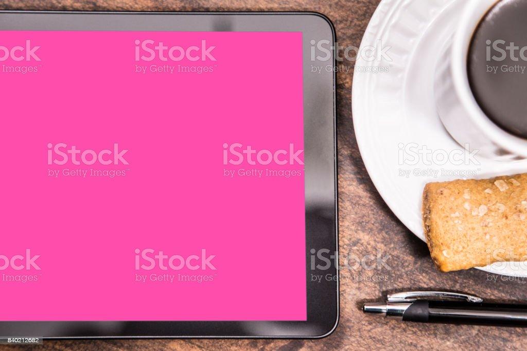 Écran de la tablette numérique blanc rose sur le bureau u photos