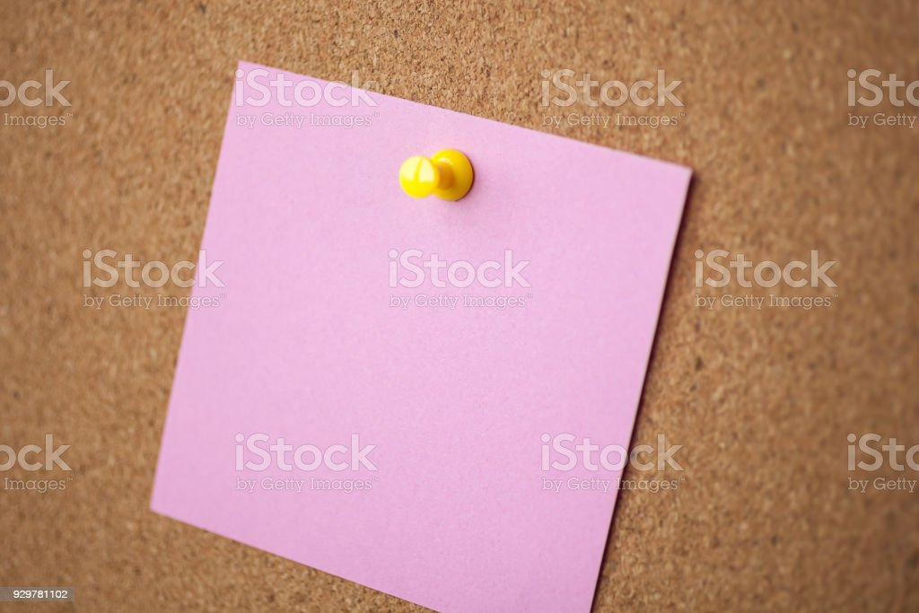 Blank pink paper pin on cork board background for remind stock photo