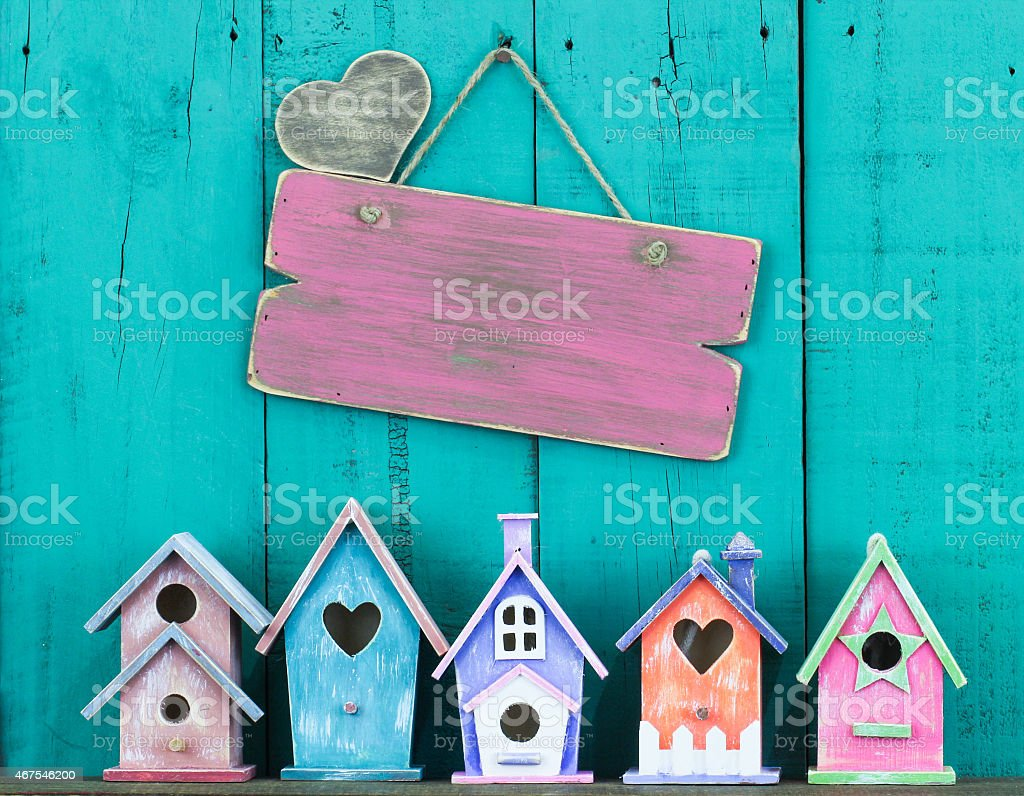 Blank pink sign hanging over mini pastel bird houses stock photo
