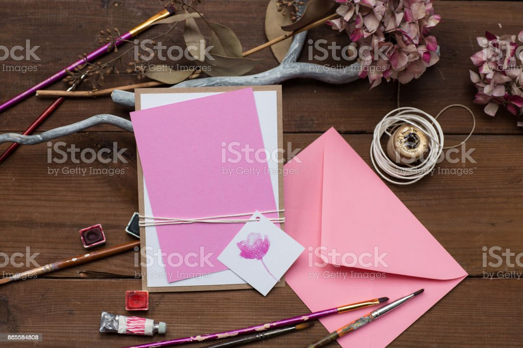 Blank pink wedding invitation or greeting card with art supplies laying around the table. stock photo