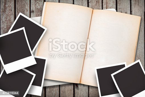 istock blank polaroid photo and opened notebook on wood ground 471915044