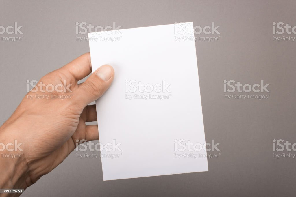 Blank postcard in hand on a gray background. Leaflet A6 mockup stock photo