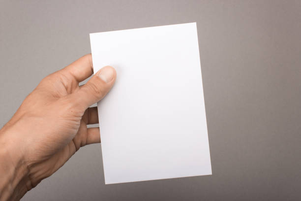 blank postcard in hand on a gray background. leaflet a6 mockup - postcard template stock photos and pictures