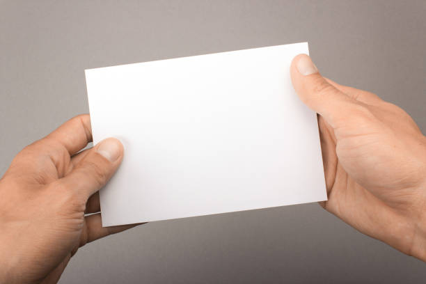 blank postcard in hands on a gray background. leaflet a6 mockup - postcard template stock photos and pictures
