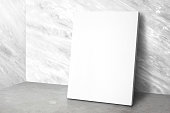 Blank poster at corner studio room with marble wall and concrete floor background,Mock up studio room for display or montage of product for advertising on media,Business presentation..
