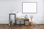 Freelancer home studio interior. Wooden desk. Blank picture poster frame. Artist designer background template.