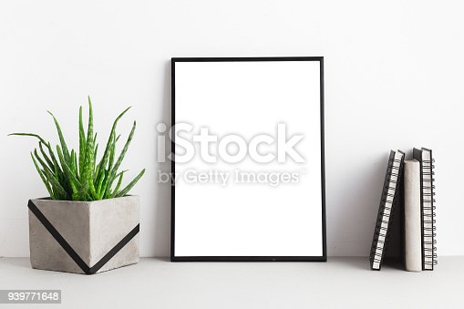istock Blank poster frame isolated on a bookshelf with books and a houseplant. Mock up 939771648