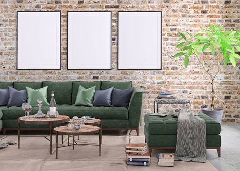 Blank poster picture frame hung on the brick wall, with large sofa with many books and details around. copy space blank designer artist background