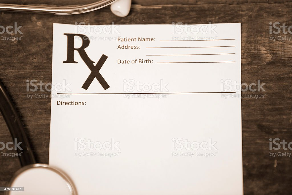 Blank prescription pad with stethoscope on doctor's desk. stock photo