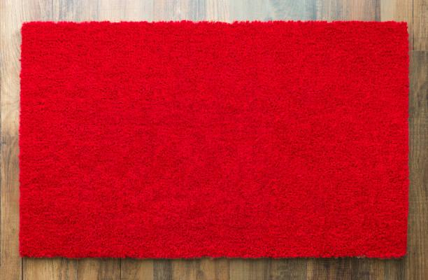 Leere rote willkommene Matte auf Holzboden Hintergrund bereit für Ihren eigenen Text – Foto