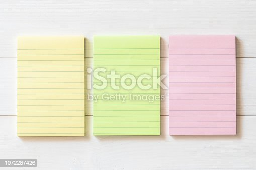 1090161334 istock photo Blank reminder paper pad with horizontal line stripes on white wood 1072287426