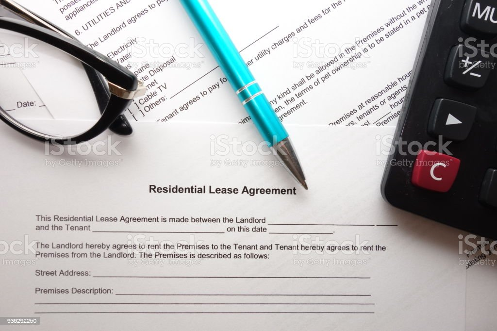 Blank residential lease agreement with pen, calculator and glasses