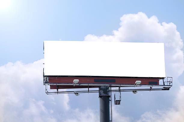 Blank roadside billboard on bright sunny blue sky day stock photo