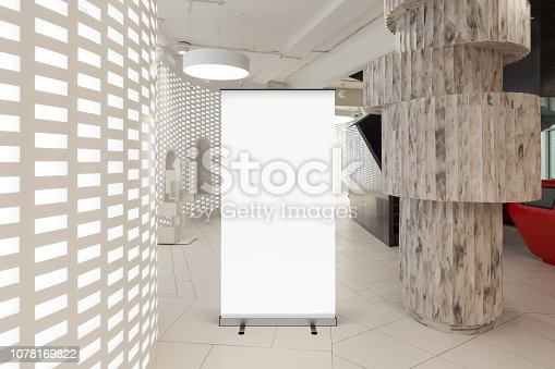 istock Blank roll up banner stand in contemporary office interior 1078169822