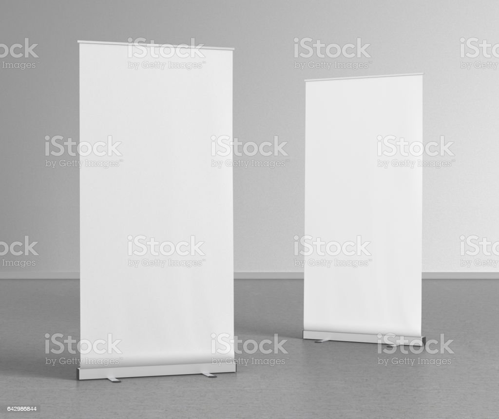Blank roll up banner stands on gray floor stock photo