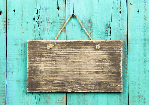 Blank rustic sign hanging on distressed wooden turquoise fence