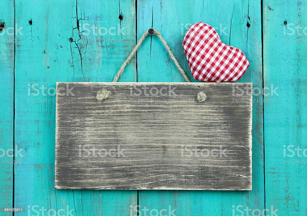 Blank rustic sign with red heart hanging on wooden background stock photo