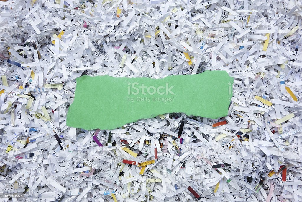 A blank torn scrap of green paper lying on top of a pile of shredded...