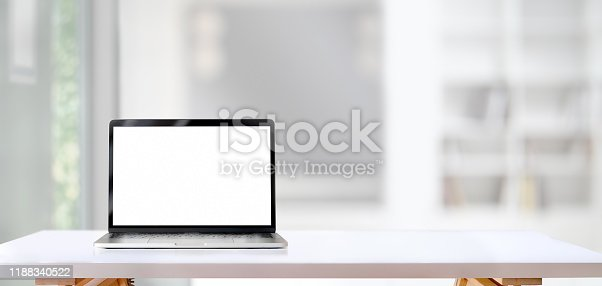 Open blank screen laptop computer on white wooden table with living room in the background