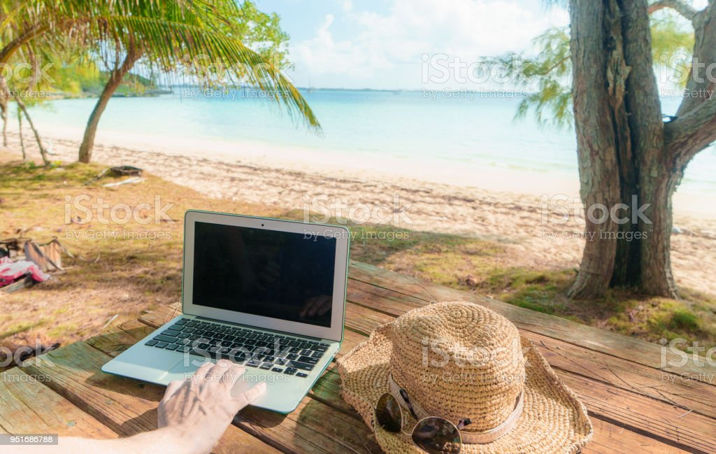 Blank Screen Laptop on Table at Beach stock photo