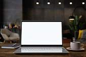 istock Blank Screen Laptop On The Table With Blurred Living Room Background At Night. 1297540300