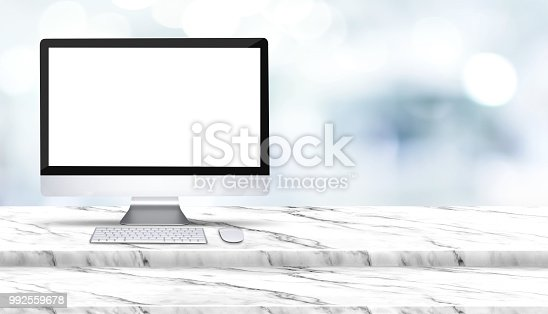 istock Blank screen of desktop computer on step white marble table with blur hospital at background,Mock up template for display of design,Banner for advertise of health care business product,panoramic. 992559678