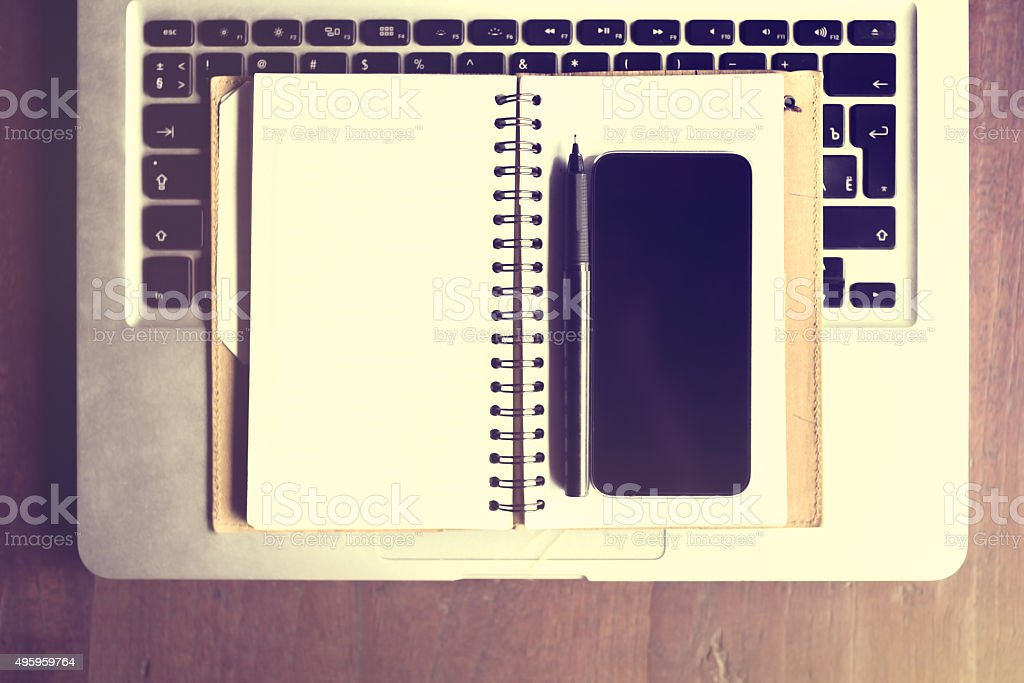 Blank screen of smartphone with diary and laptop keyboard, insta stock photo
