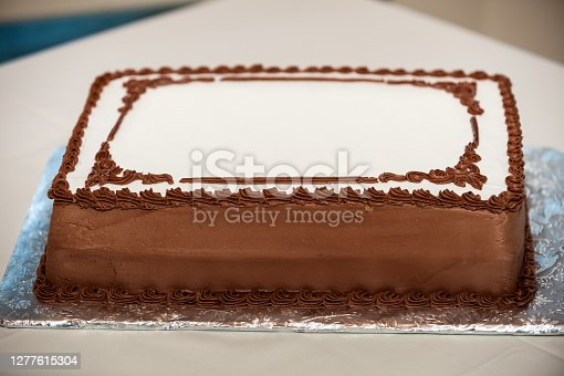 Blank Sheet Cake with Chocolate Trim Icing on aluminum foil.