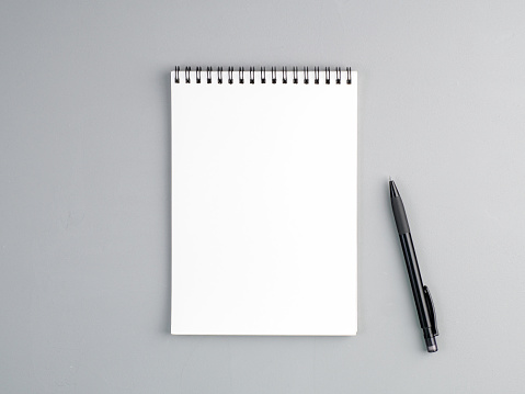 istock blank sheet of notebook with a spiral and pen on a neutral gray textured  background 942930688