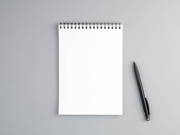 pusty arkusz notebooka ze spiralą i piórem na neutralnym szarym tle teksturowanym - notes zdjęcia i obrazy z banku zdjęć