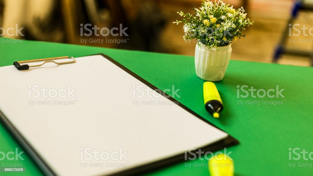 Blank sheet of paper for records, a yellow felt-tip pen and flowers, on a green table. Working notes. Copy space. Mockup stock photo