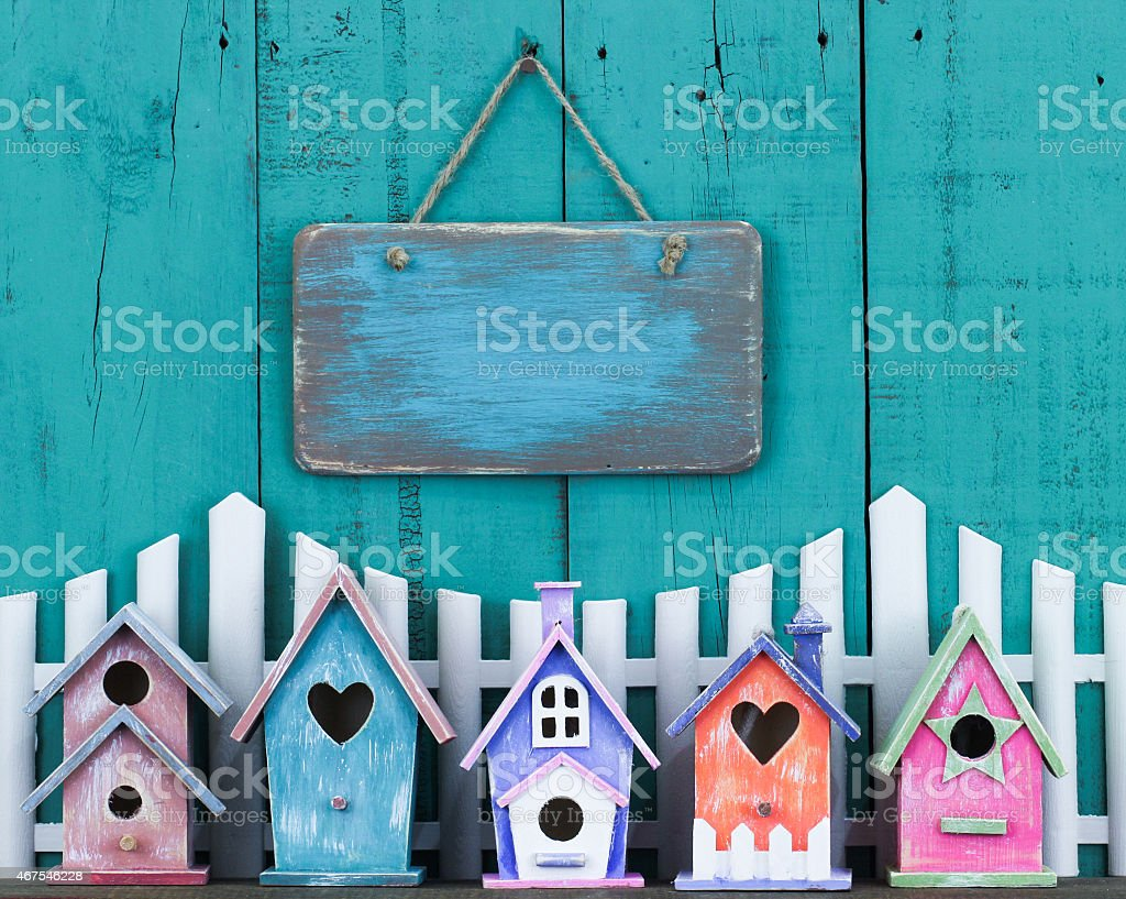 Blank sign hanging over fence and colorful birdhouses stock photo