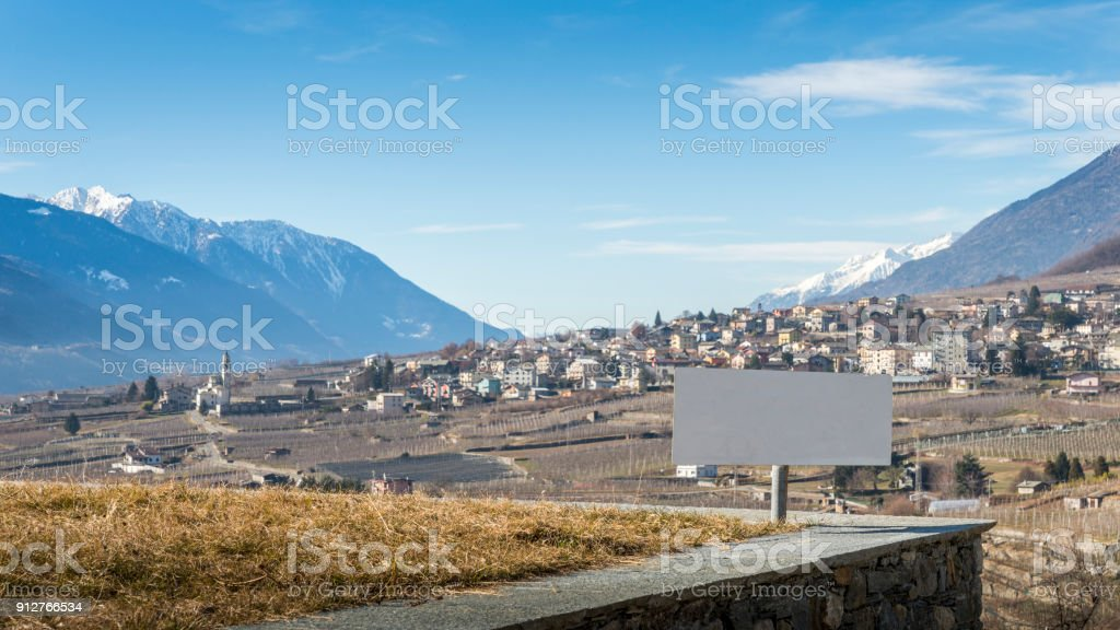 Blank sign overlooking vineyards above Sondrio, an Italian town and comune located in the heart of the wine-producing Valtellina region stock photo