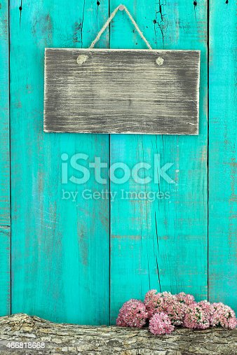 Blank rustic sign hanging on antique teal blue wood fence with log and flower border