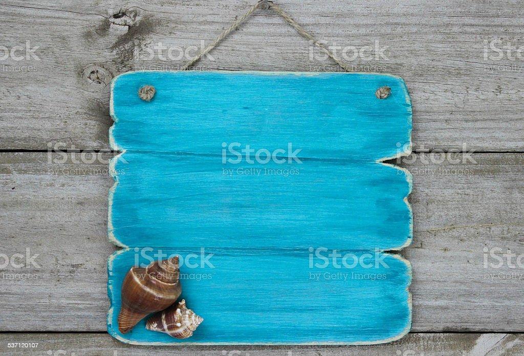 Placa em branco com conchas pendurado na porta de madeira - foto de acervo