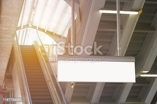 1166703050 istock photo Blank signboard horizontal in subway station with escalator background. It is direction signage mock up for information public transport. 1167735251