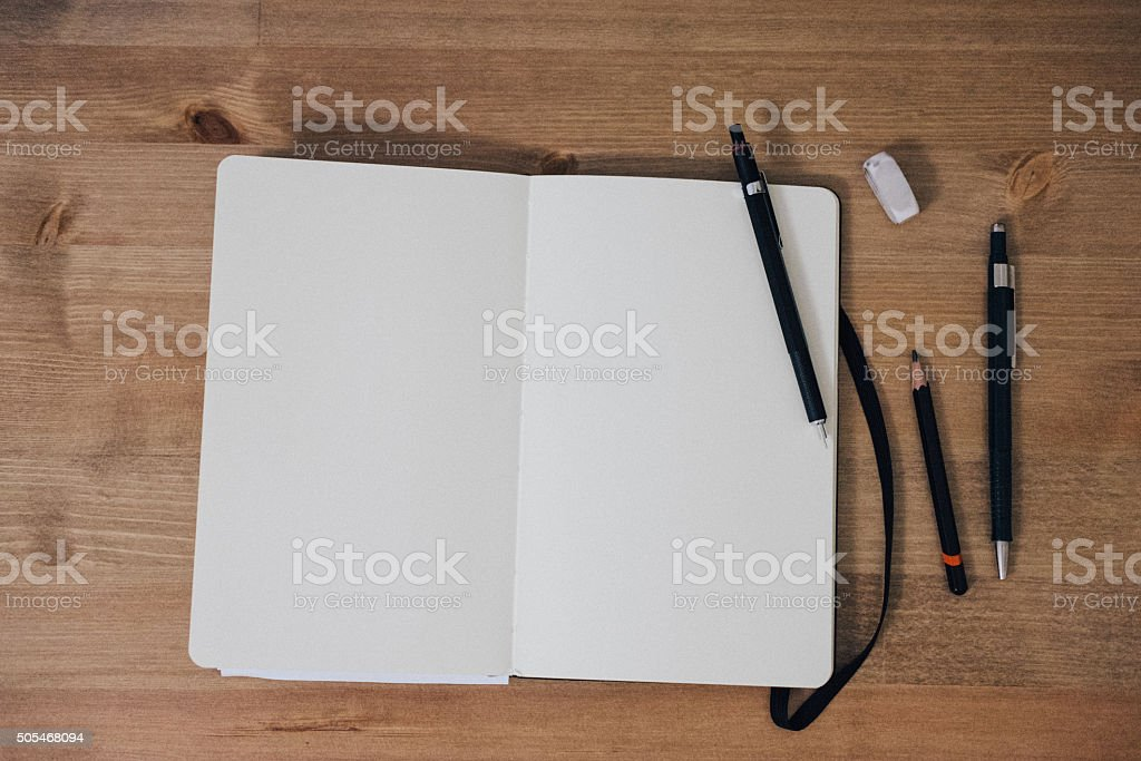 Blank sketchbook on wooden table with crayons stock photo