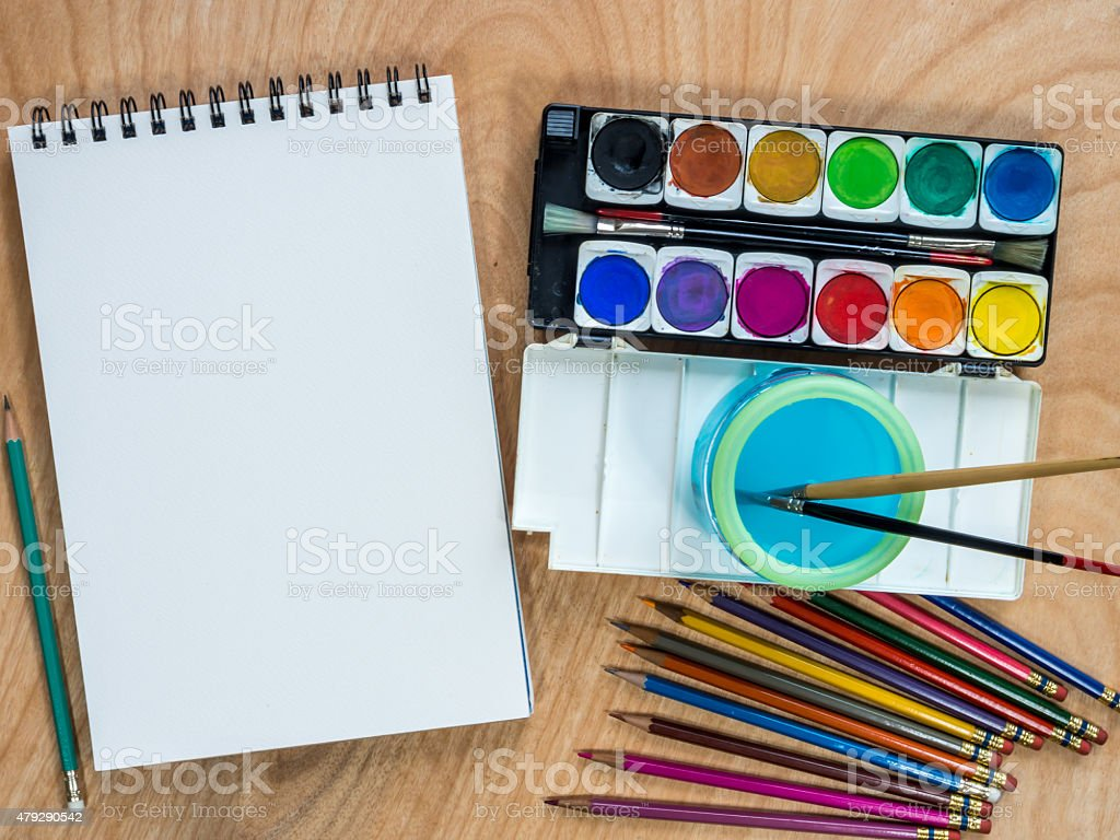 Blank  sketchbook, watercolor paints, color-pencils for painting on wooden table stock photo
