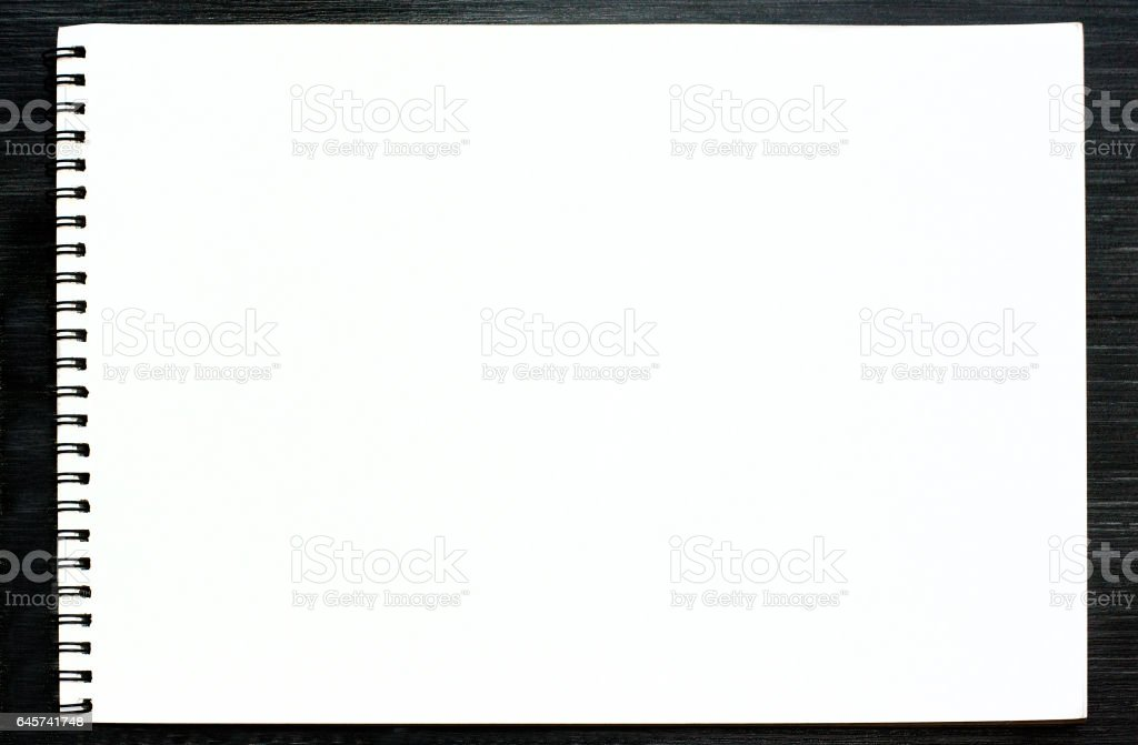 Blank sketchbook with white pages on black wooden table stock photo