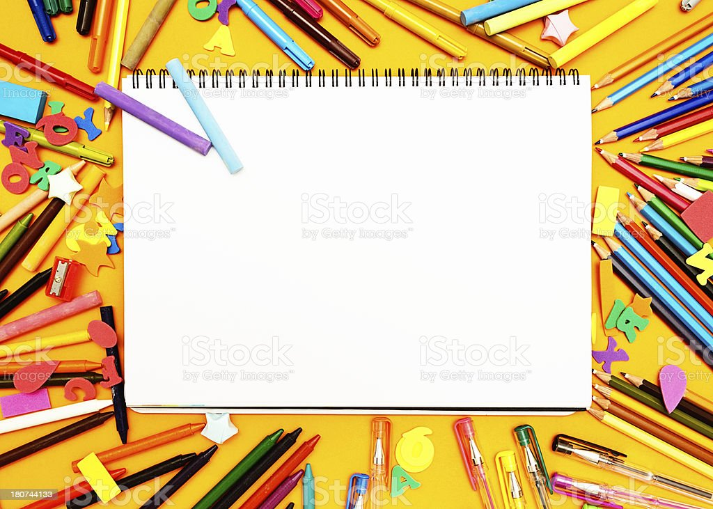 Blank sketchpad framed by multiple drawing and writing materials royalty-free stock photo