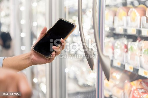 An unrecognizable person, with just hands showing, holds up a smart phone with a blank screen while grocery shopping.  A refrigerator with deli meat can be seen in the background.