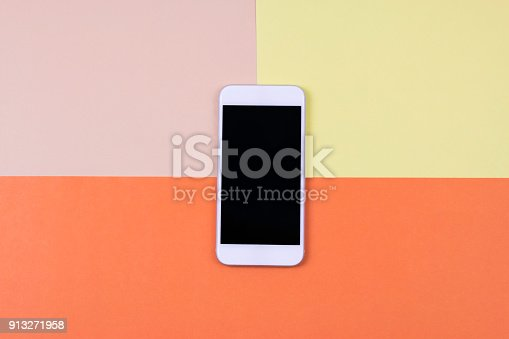 istock Blank smart phone on cream, yellow and orange background. 913271958