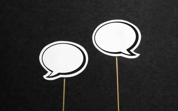 2 blank speech bubbles on a dark black background. Chat bubble cut from paper with wooden stick. Fun discussion, protesting and commenting concept. stock photo